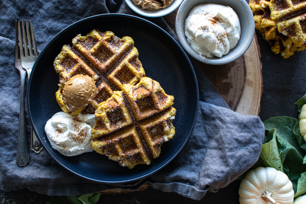 Two pumpkin Liege waffles on black plate topped with speckluloos and whipped cream