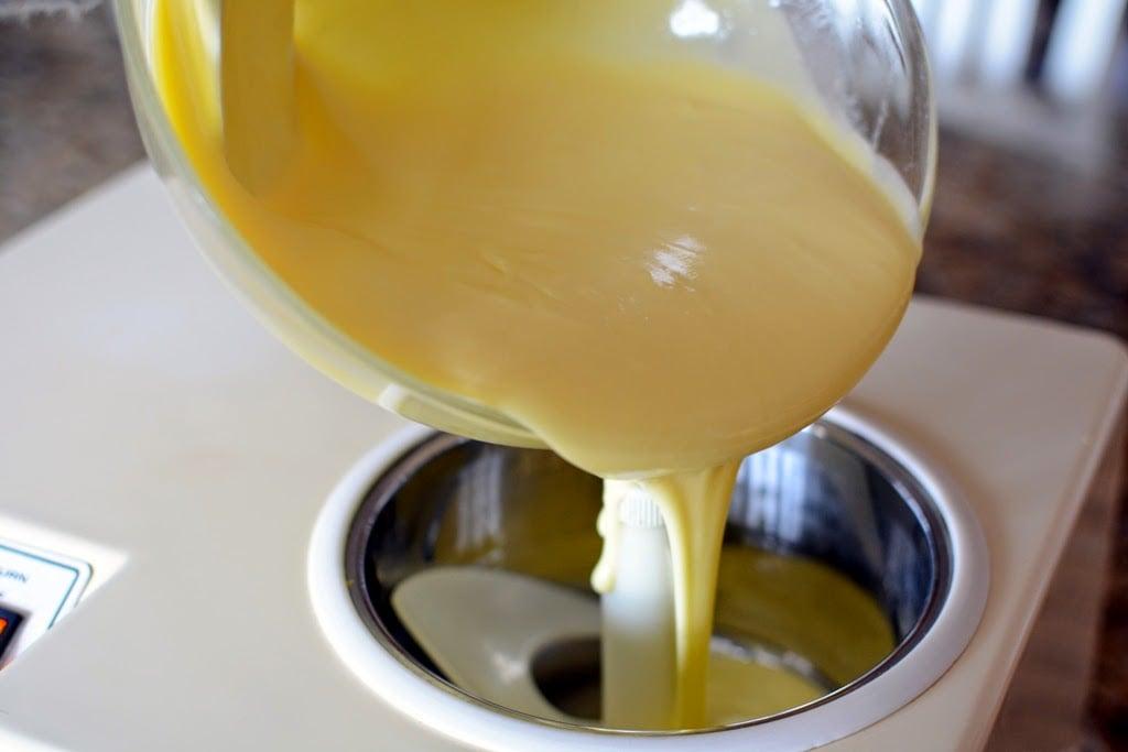 Golden vanilla ice cream pouring into ice cream maker