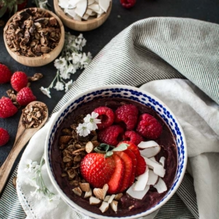 Acai bowl with fresh berries on a striped cloth with granola and coconut in small wooden bowls