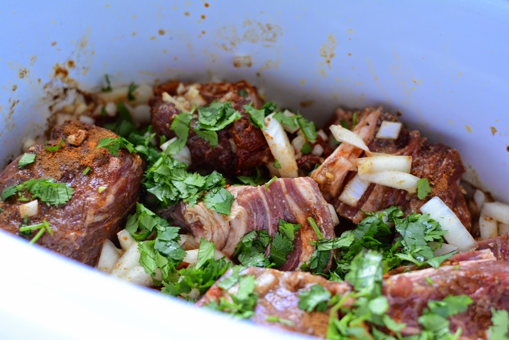 uncooked beef with spices and cilantro in crockpot