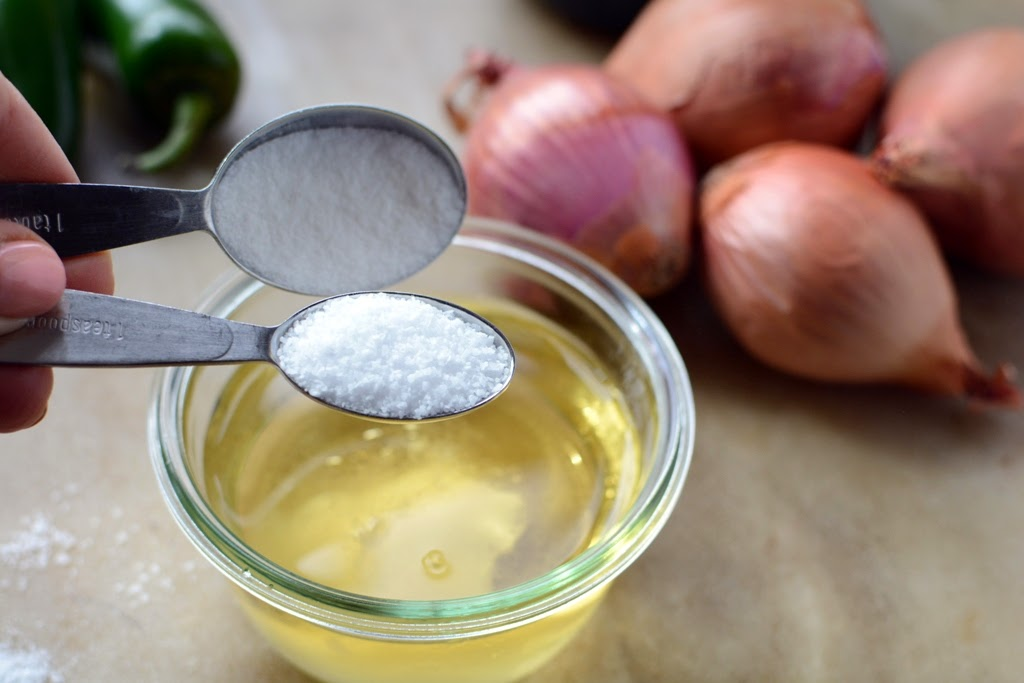 bowl of vinegar with sugar being added