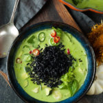 overhead shot of bright green curry with slices of hot peppers with black rice on top