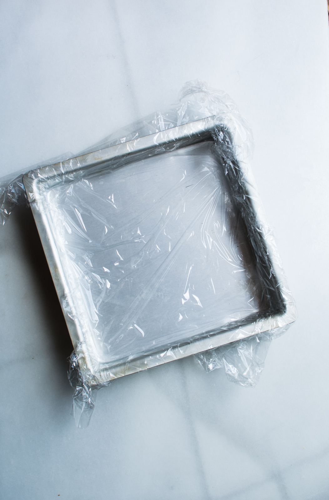 baking pan lined with plastic wrap