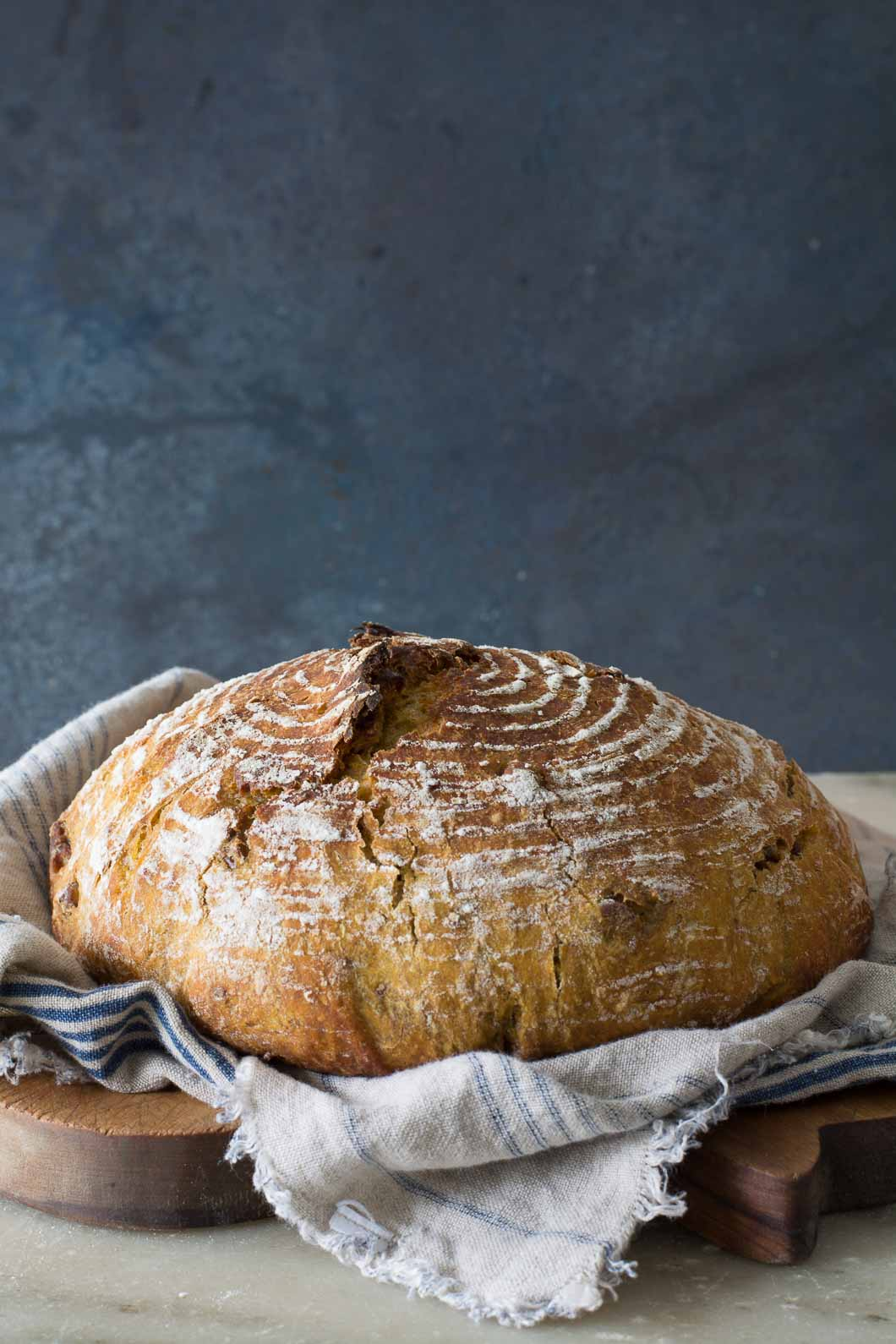 o-Knead Pumpkin Pecan Bread sitting on a bread board under a cloth