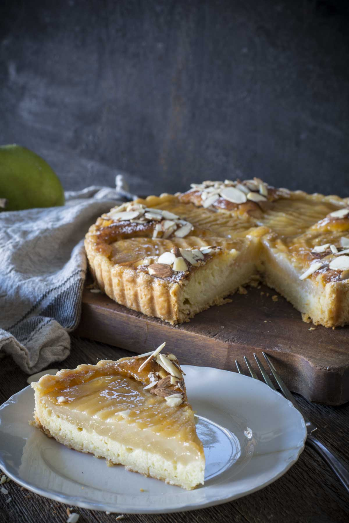Slice of Pear Almond Tart on a white plate with pie in background