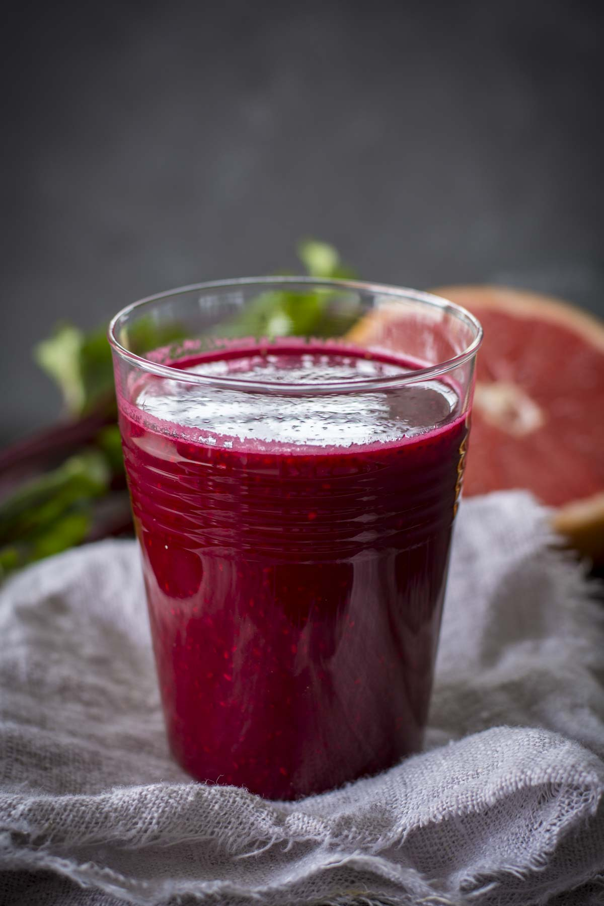 chia beet grapefruit juice in a glass with grapefruit in background