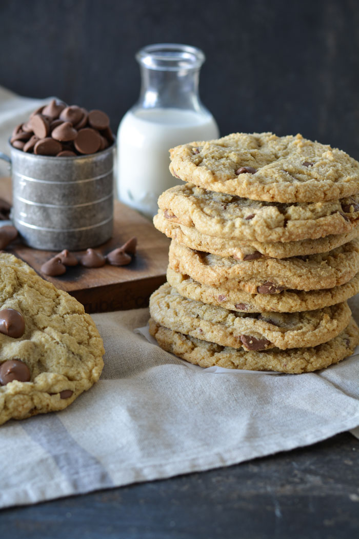 Jumbo size chocolate chip cookies stacked with bottle of milk
