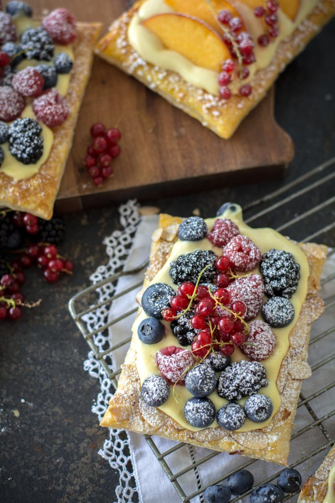 Easy Fresh Berry Puff Pastry Tarts on a cooling rack with white cloth