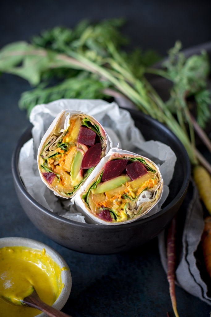 Beet, Peach, and Avocado Wrap with Turmeric Tahini Sauce cut in half in a black bowl