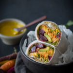 Beet, Peach, and Avocado Wrap with Turmeric Tahini Sauce in a black bowl