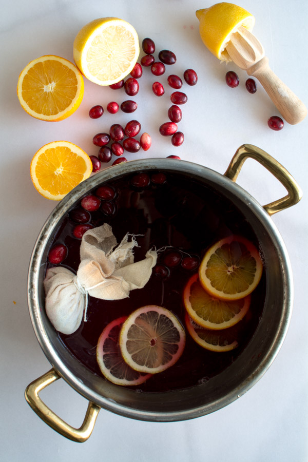 Cranberry wassail in a pot with scattered cranberries, orange slices