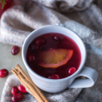 Cranberry wassail in a mug with cinnamon stick and cranberries