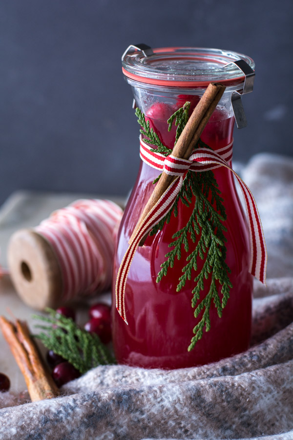 Cranberry wassail in a jar with spool of ribbon in background and cinnamon stick