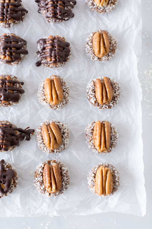 Date bites with whole pecans on parchment