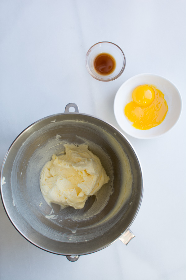Bowl with butter mixture, egg yolks, vanilla, in bowl
