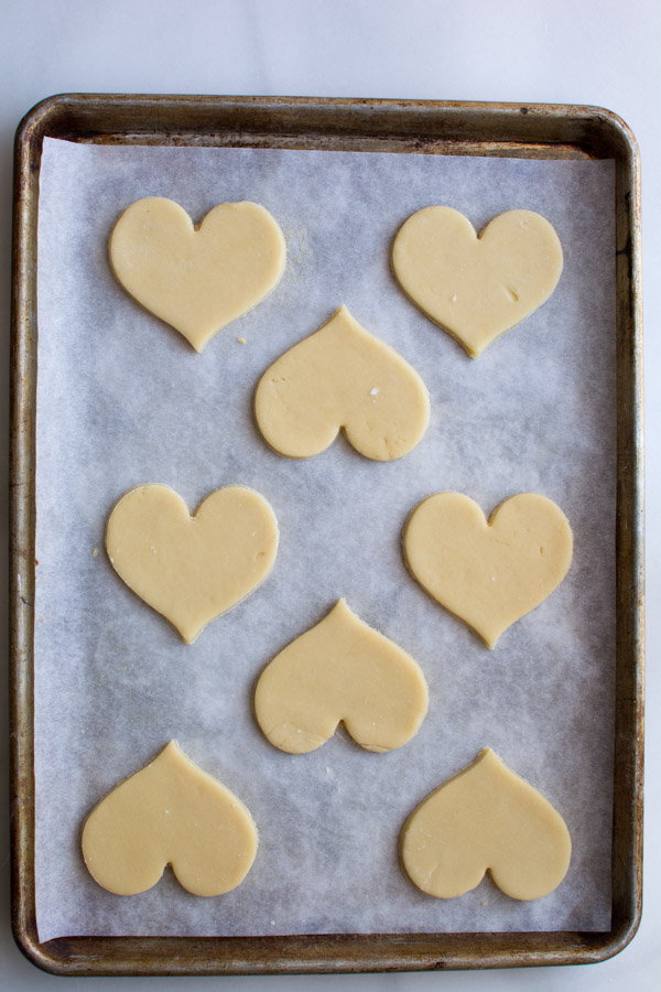 heart shaped cookie dough on baking sheet