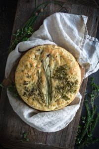 Round focaccia bread topped with an arrangement of fresh herbs on a cloth and bread board
