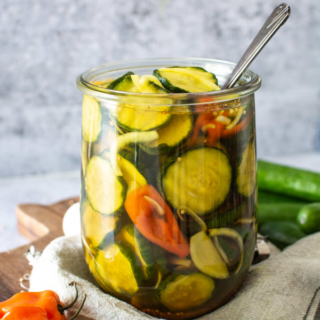 large jar of spicy sweet pickles with habanero peppers and onions