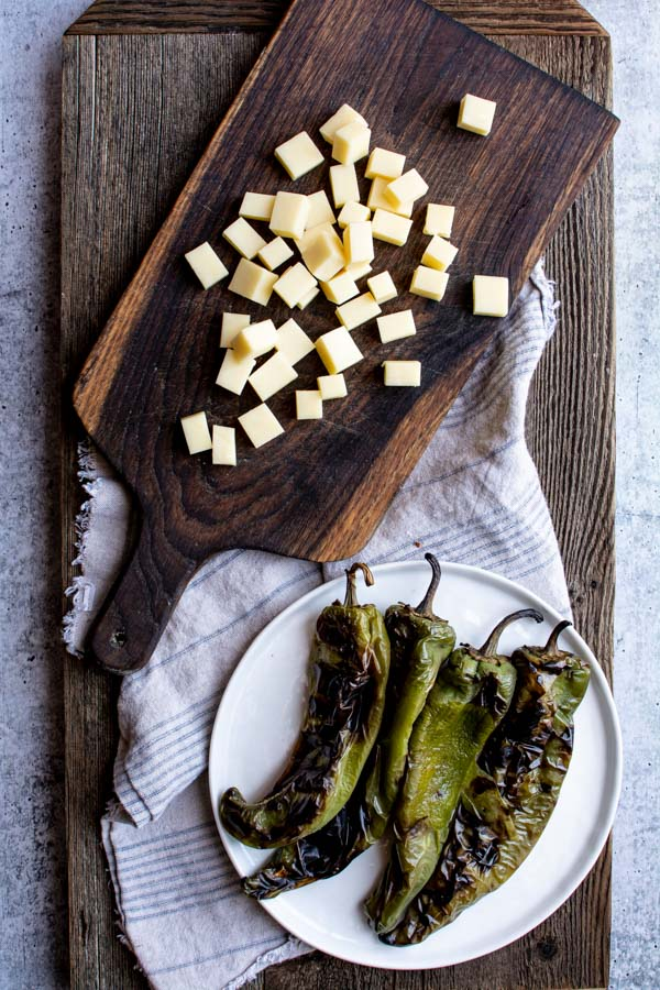 Cubed white cheddar on cutting board next to plate of roasted green chiles
