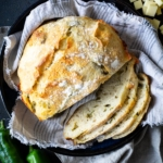 Partially sliced No-Knead Green Chile Cheddar Bread on tan cloth in blue bowl