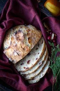 overhead shot of sliced cranberry orange pecan bread on a burgundy cloth