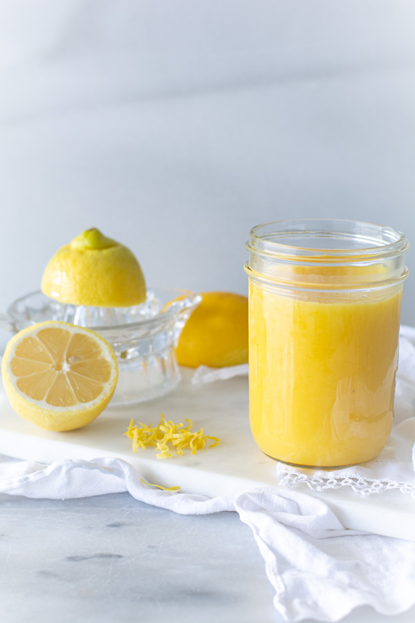 Jar of lemon curd on white cloth and sliced lemon