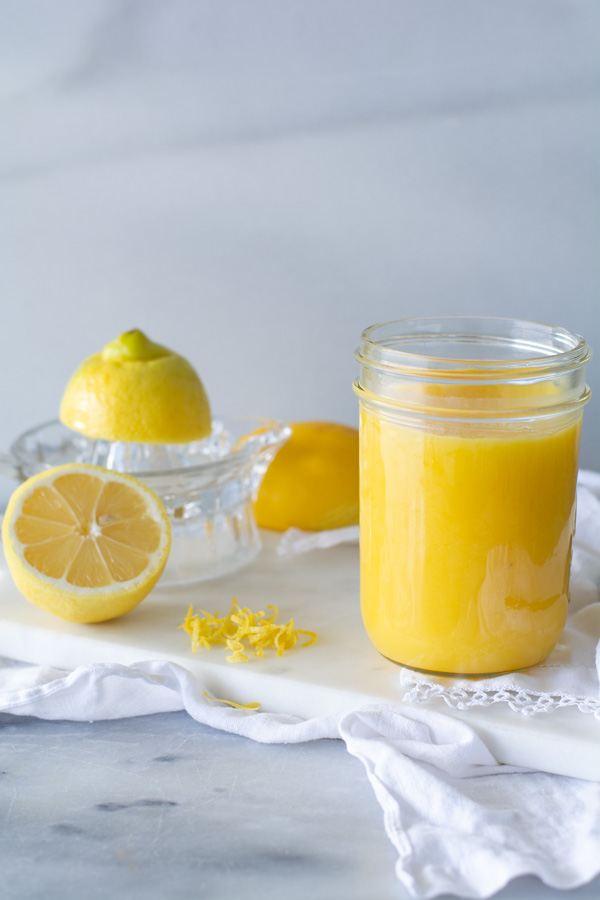 jar of lemon curd on white cloth with fresh lemons in background