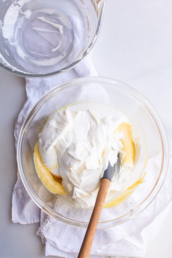 Whipped cream on top of bowl with lemon curd mixture