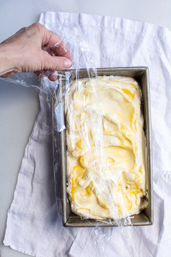 Plastic wrap covering pan with ice cream