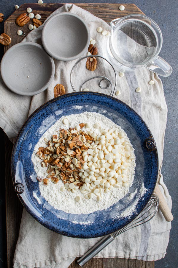 blue bowl with flour , pecans, white chocolate chips