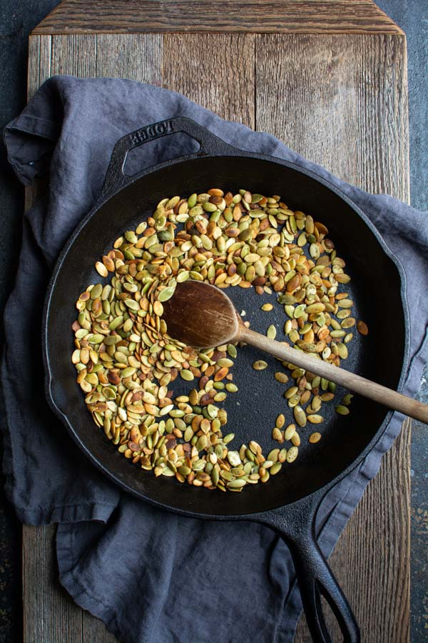 Cast iron skillet with toasted pumpkin seeds and wooden spoon