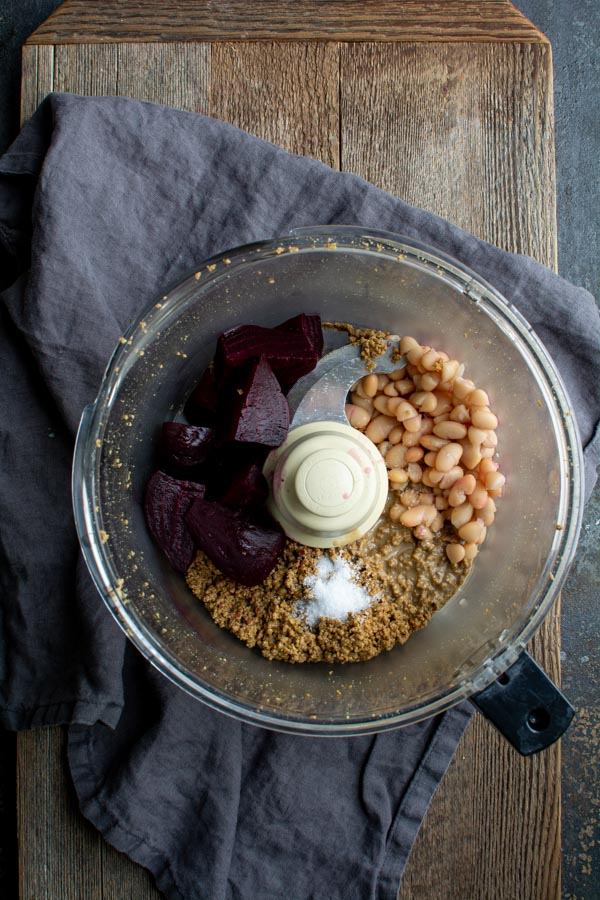 food processor bowl with ground pumpkin seeds, beets, and white beans
