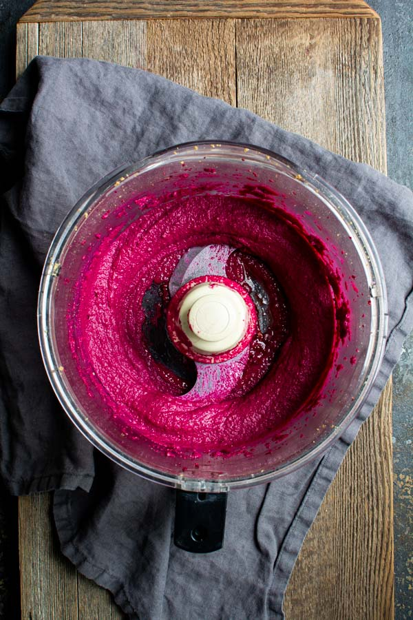 Food processor bowl with bright pink beet butter