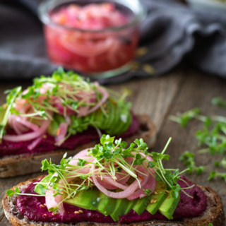 two slices bread spread with beet butter, sliced avocados, and pickled onions