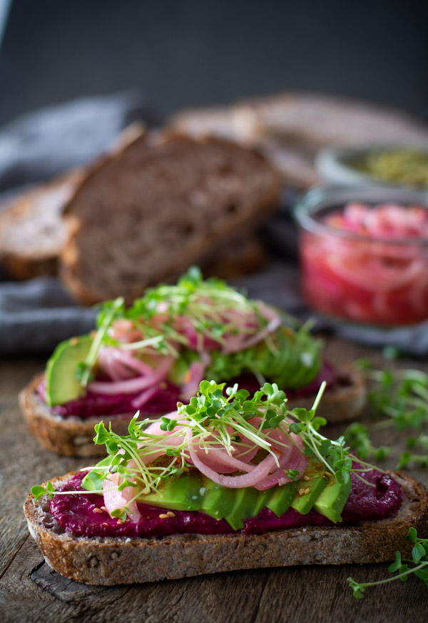 Two slices of bread layered with beet butter, avocado, pickled onions