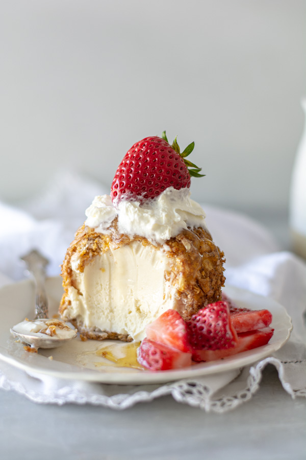 fried ice cream with spoonful taken out with honey and berries