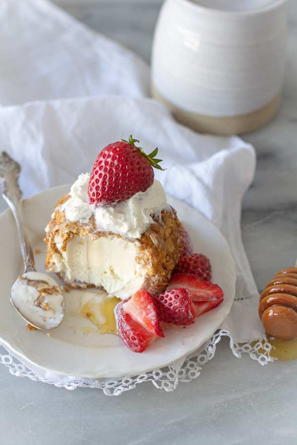 Mexican fried ice cream with strawberries, on a white plate with honey drizzle and honey stick