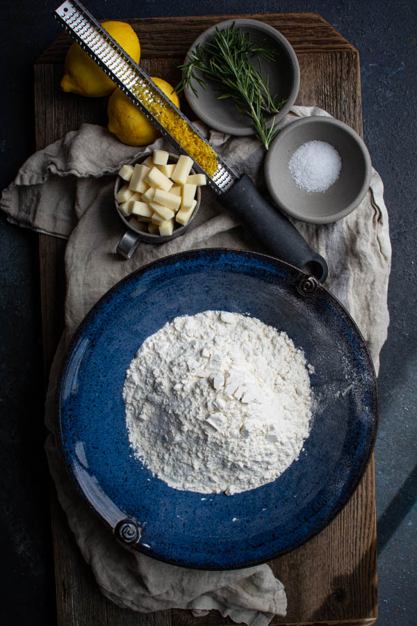 blue bowl with flour surrounded by cubed cheese, lemon zest, rosemary