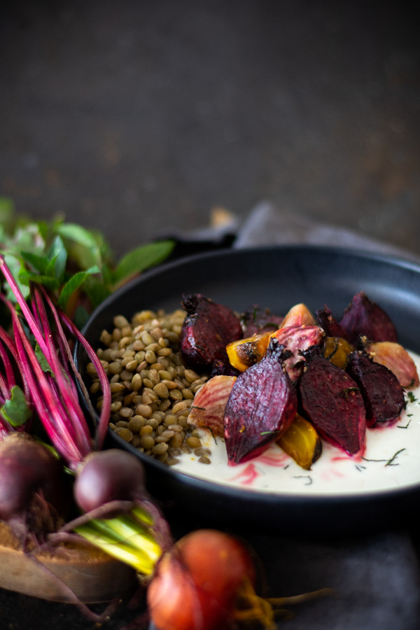 Black bowl with mint yogurt topped with roasted beets and chopped mint