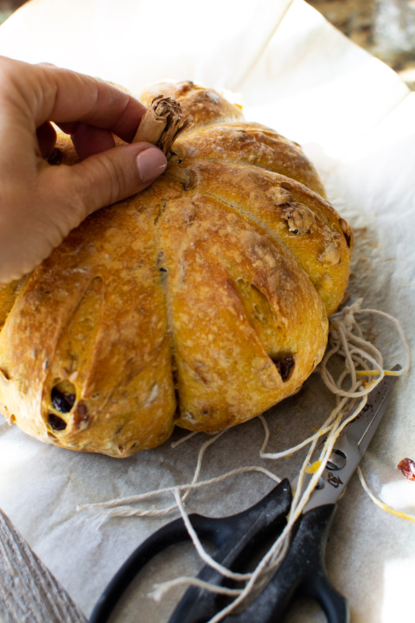 baked pumpkin shaped bread with a cinnamon stick stem being poked into the center