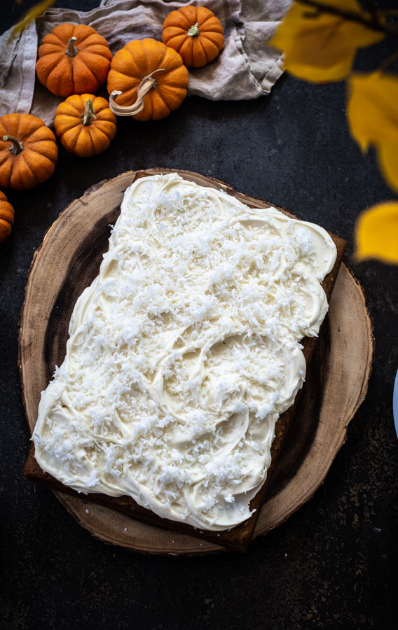 Overhead shot of pumpkin cake spread with cream cheese icing topped with flaked coconut