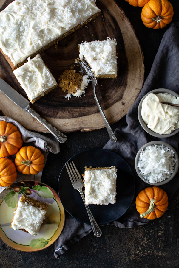 Overhead shot of pumpkin coconut cake on a wood slab with pumpkins scattered around and a bowl of icing and coconut.