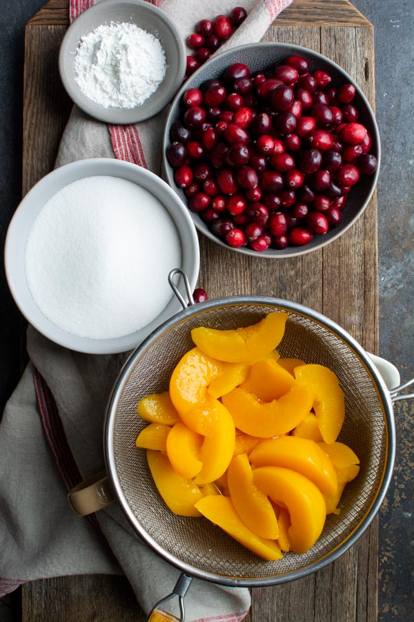 Wire strainer with peaches, bowl of cranberries