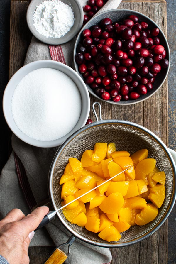 Wire strainer with peaches cutting with a knive