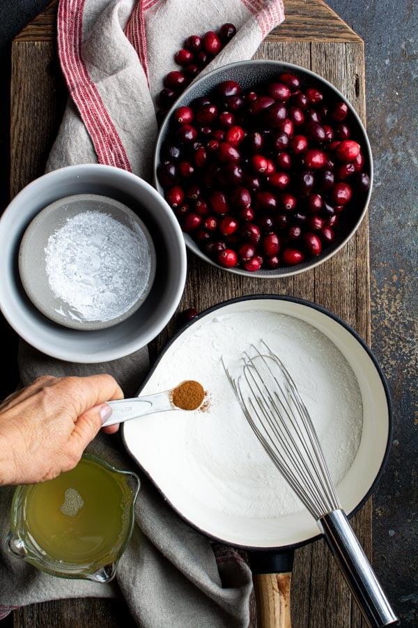 Saucepan with sugar and cinnamon, bowl of cranberries
