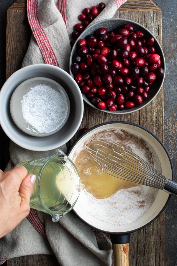 saucepan with peach juice added to sugar mixture, bowl of cranberries