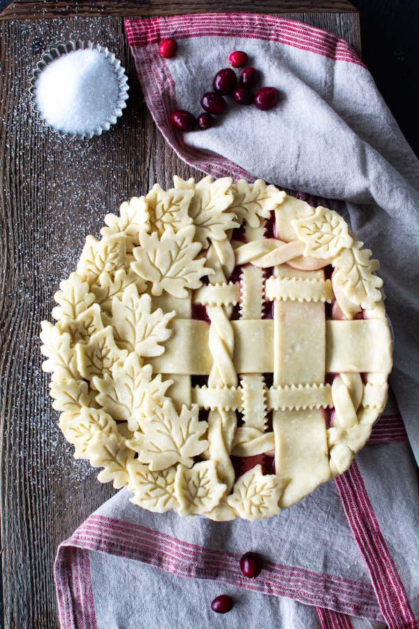 Decorative lattice on cranberry peach pie, sanding sugar, and cranberries