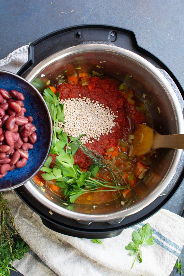 A slow cooker with sauteed vegetables, broth, barley, tomatoes and fresh herbs