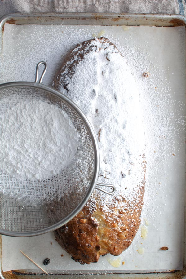 Large sieve sifting powder sugar over baked Stollen