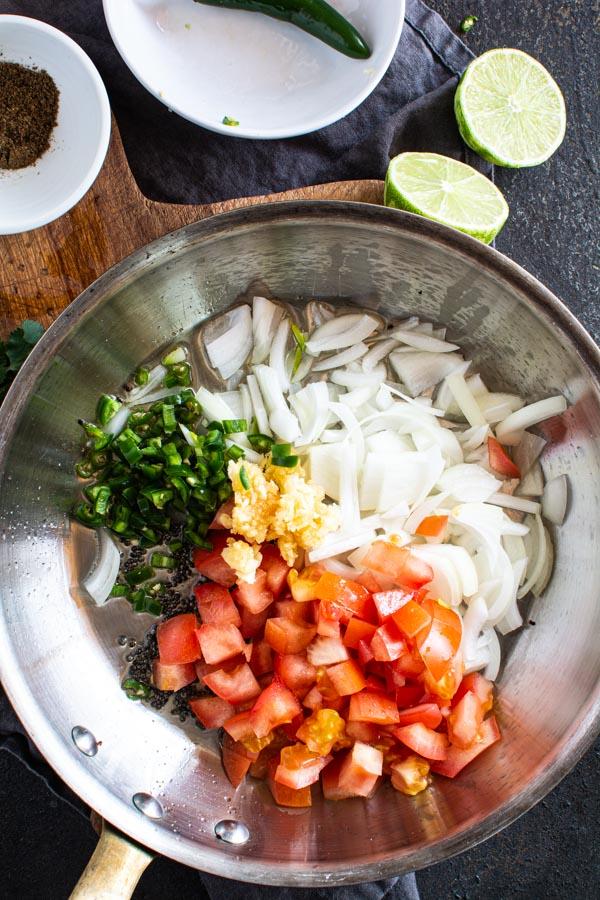 chilies, tomatoes, onions, garlic in sautee pan